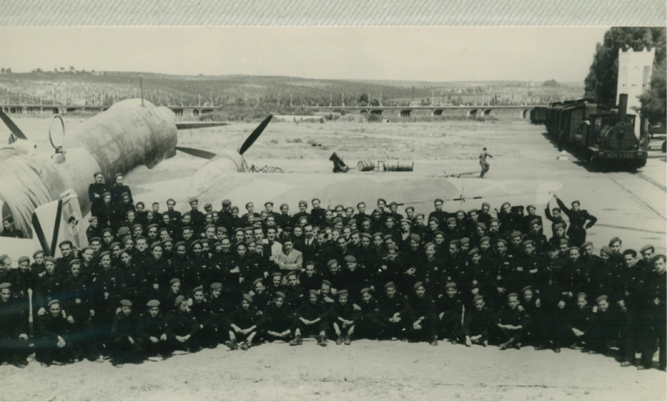 Foto de la Primera Promoción de la Escuela de Aprendices en la Maestranza Aérea. A la derecha, se puede ver el tren de los obreros y al fondo el viaducto que, prolongado por un puente de hierro, une Sevilla con San Juan de Aznalfarache